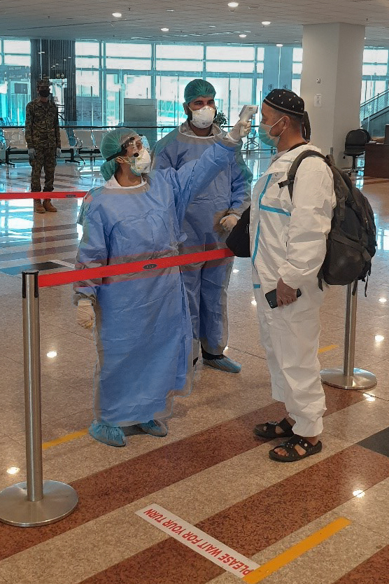 A doctor screens a traveler for COVID-19 symptoms at Islamabad Airport, Pakistan. (CDC Global/Flickr)