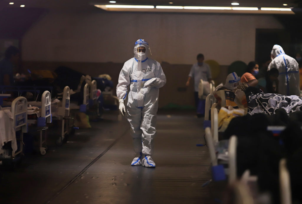 A health worker walks through at a makeshift COVID-19 quarantine facility set up at a banquet hall in New Delhi, India, on Wednesday, April 21, 2021 (Anindito Mukherjee/Bloomberg via Getty Images)