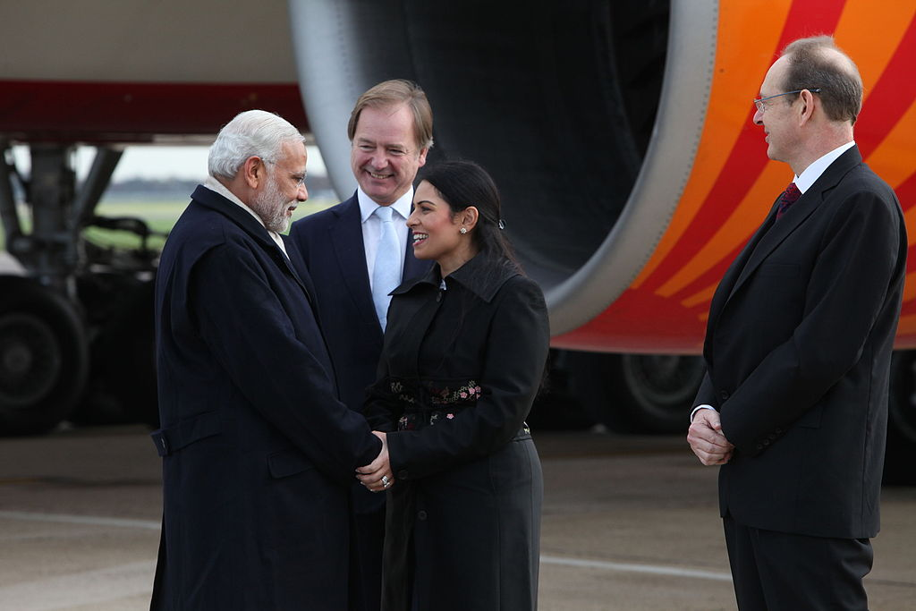 Narendra Modi is greeted by British MP Priti Patel after arriving at Heathrow Airport (Wikimedia)