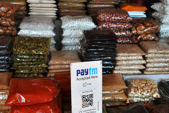 A sign for the PayTM online payment method, operated by One97 Communications Ltd., is displayed next to bags of spices at a wholesale market in Delhi, India, on Friday, Nov. 25, 2016. (Anindito Mukherjee/Bloomberg via Getty Images)