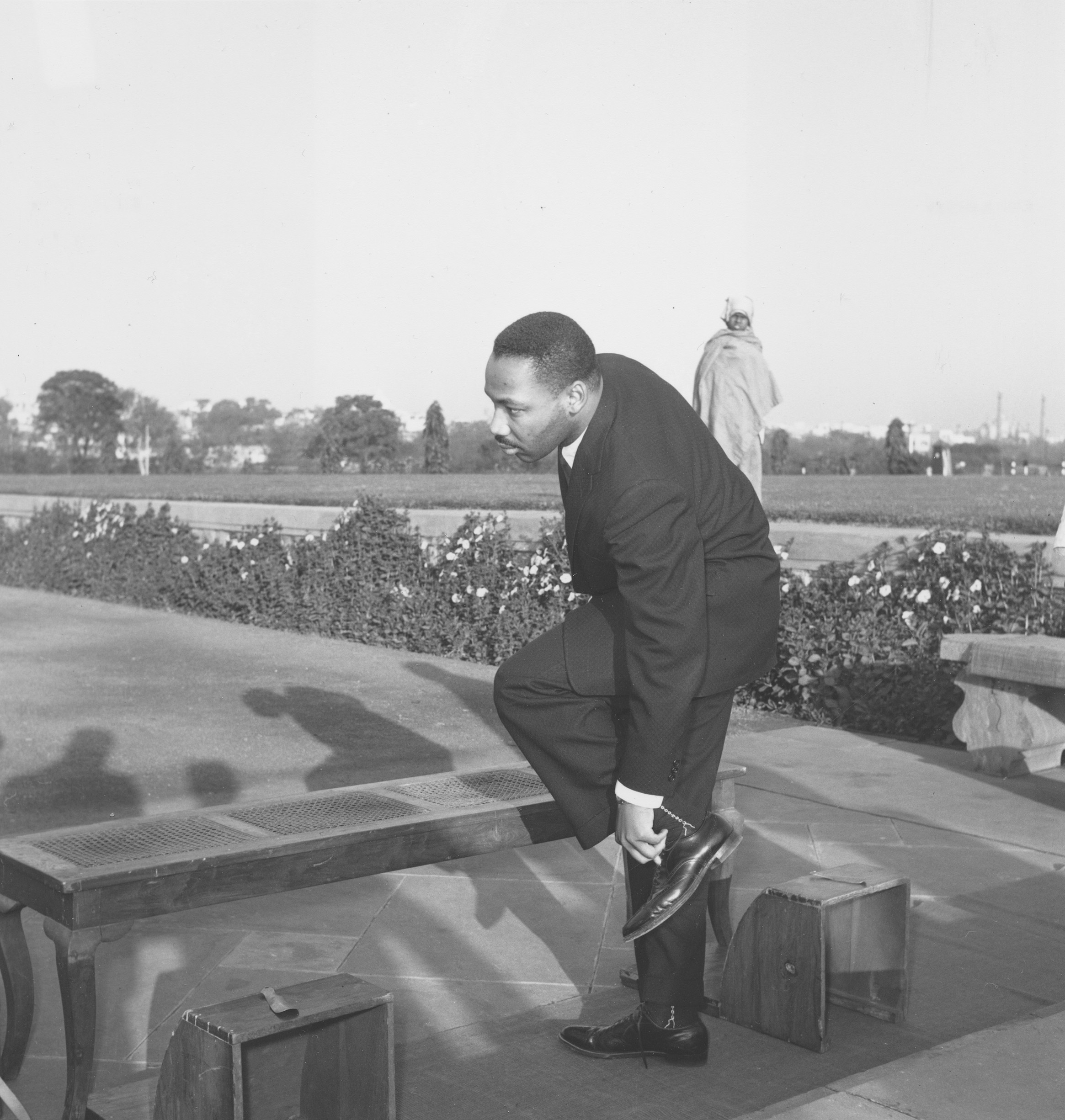 American civil rights leader Rev. Martin Luther King, Jr. removes his shoes before entering Mahatma Gandhi's shrine in New Delhi, India, Feb. 11, 1959. (AP Photo)