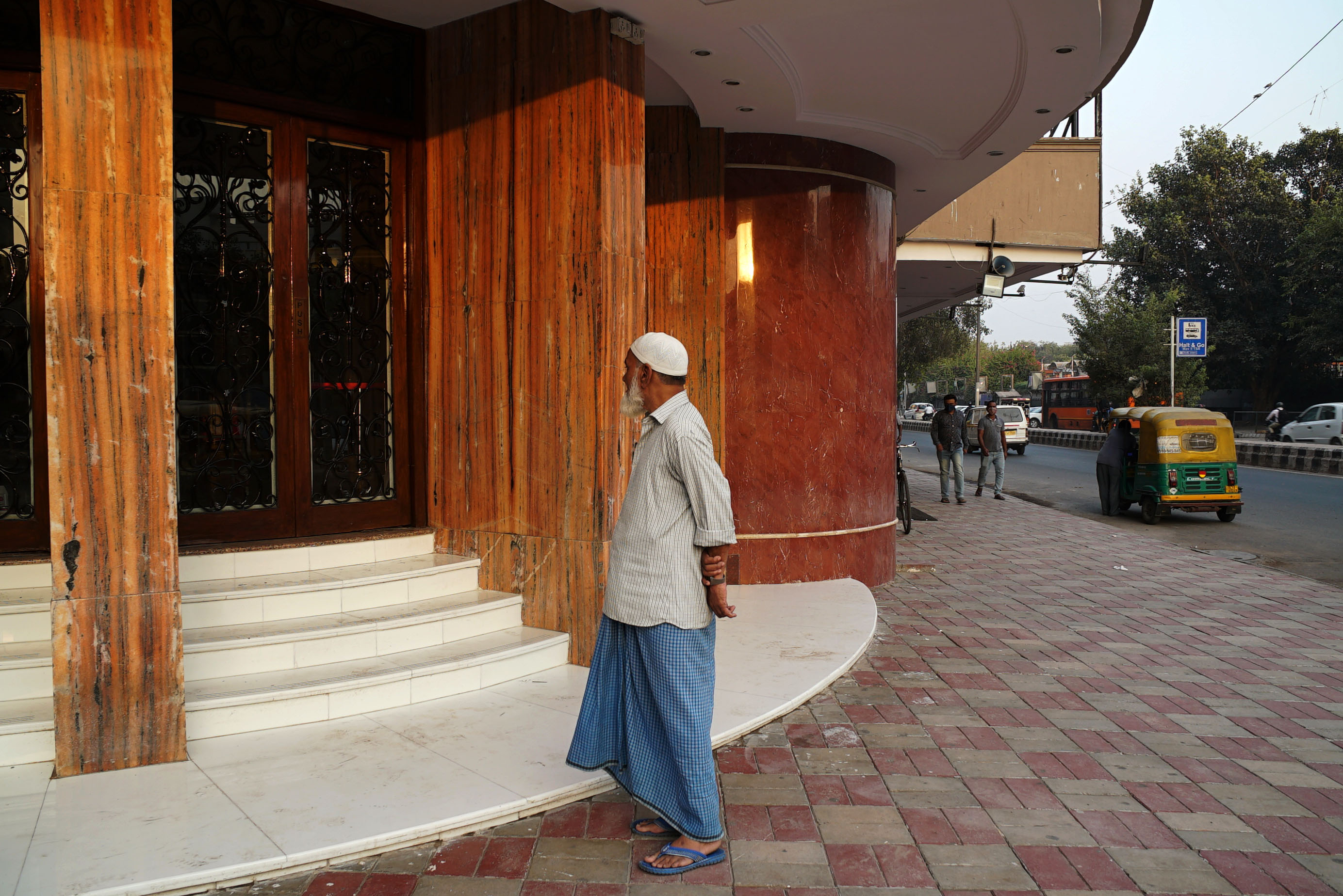 A passerby peers into the Delite cinema in Delhi, which has been closed during the pandemic. (Veda Shastri)