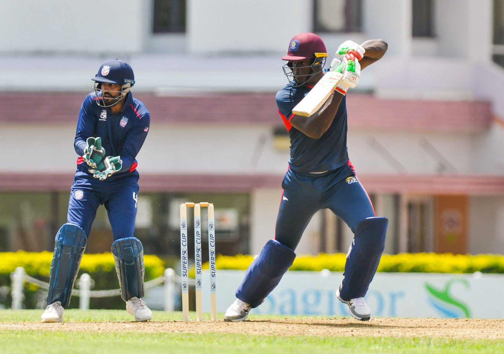 A batsman playing a cover drive as Jaskaran Malhotra looks on from behind the stumps. (USA Cricket)
