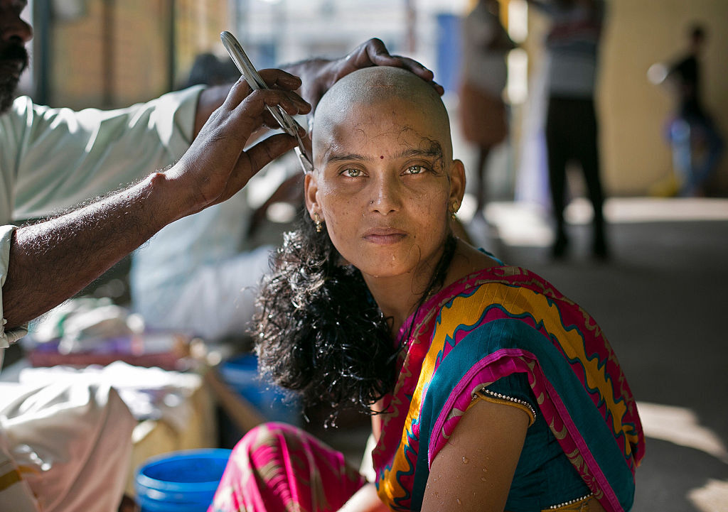 28-year-old Rupa has her hair shaved to donate at the Thiruthani Murugan Temple November 10, 2016 in Thiruttani, India (Photo by Allison Joyce/Getty Images).