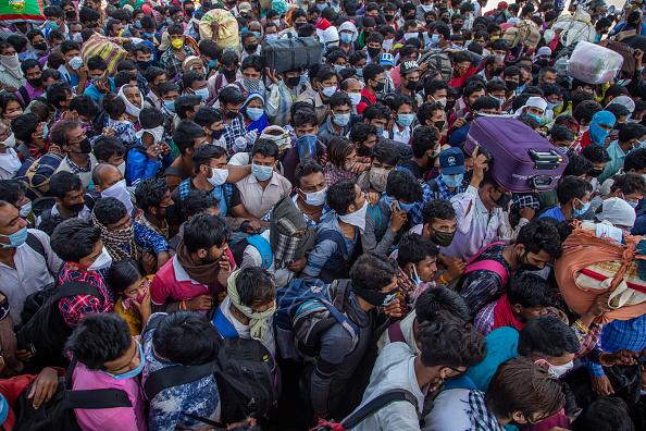 Indian migrant workers and labourers along with their families stuck in the national capital, with and without protective masks crowd to board buses to return to their native villages (March 29, 2020) (Photo by Yawar Nazir/Getty Images)