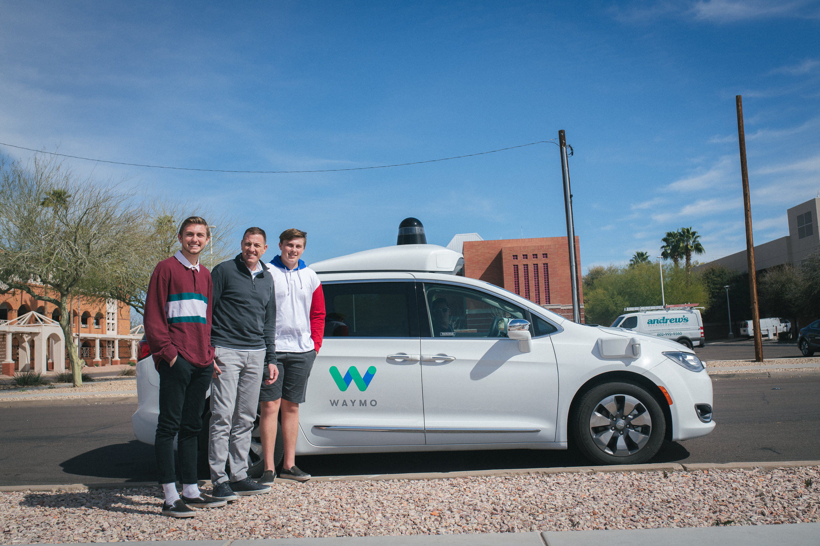 Denny Barney and sons with a Waymo vehicle