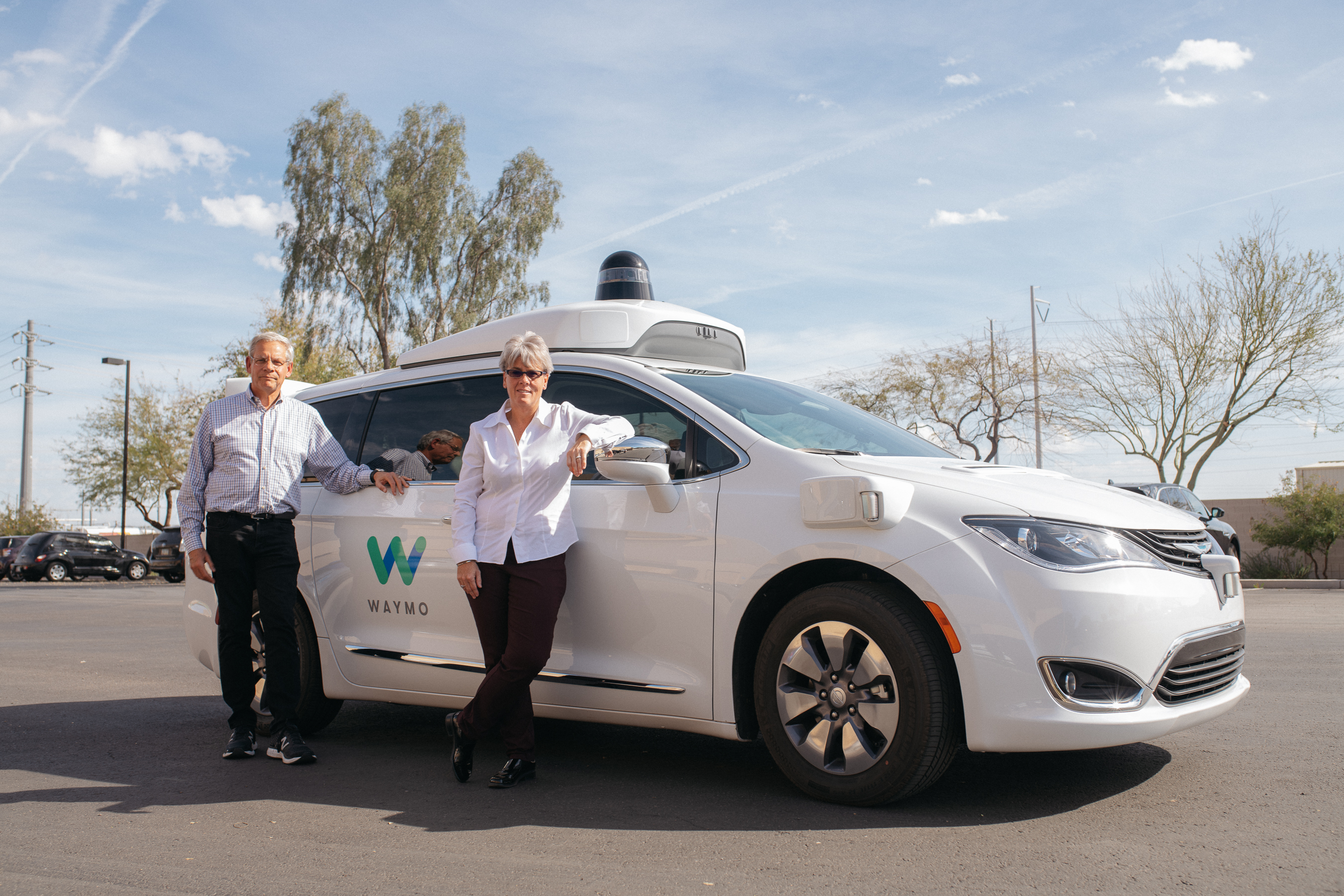 Alex Epstein and Kelly Nantel of the National Safety Council beside a Waymo vehicle
