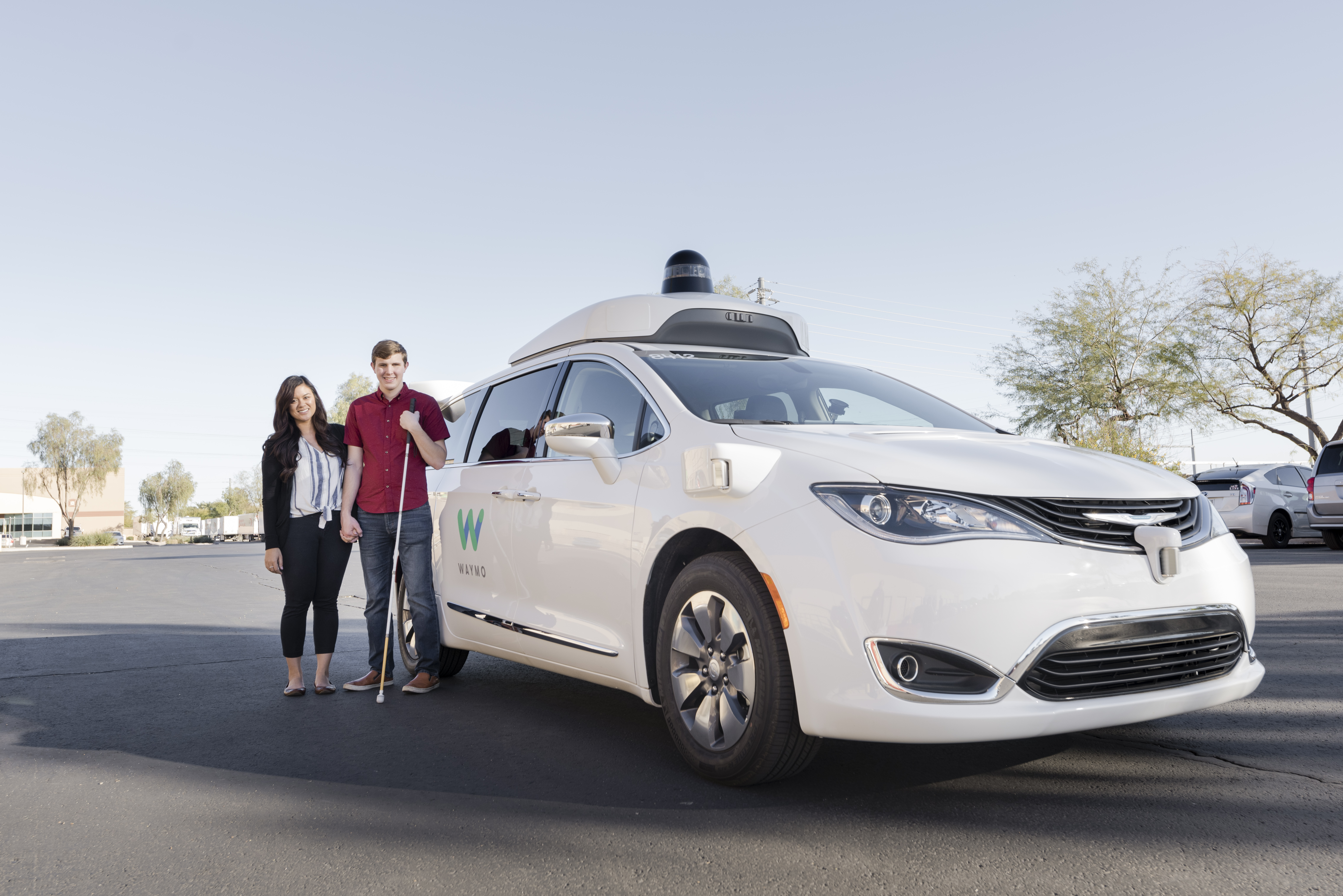 Max and Lillian standing beside a Waymo