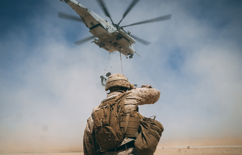 military personal below a helicopter