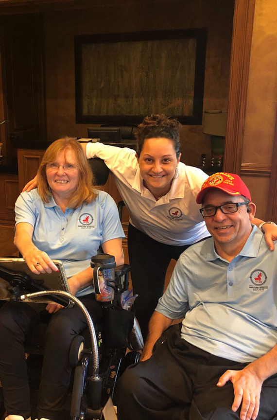 3 people smiling for a photo, two are in wheelchairs.