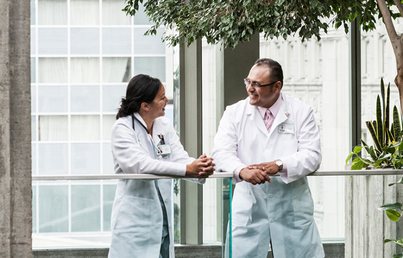 a man and woman in lab coats talking on a balcony