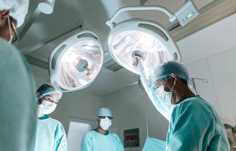 doctors in an operating room under bright lights