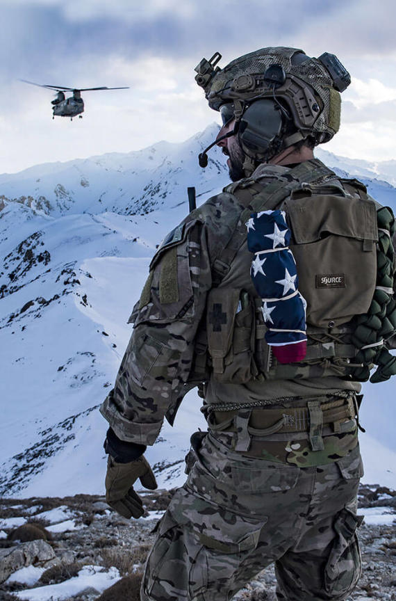 Solider standing in the mountains with a helicopter in the background