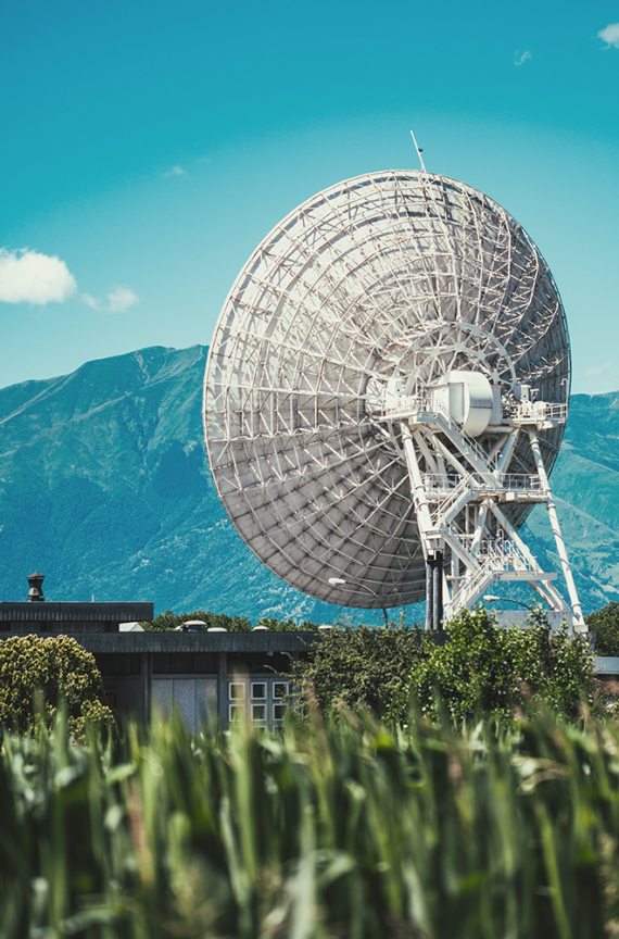 big satellite in field in front of mountains