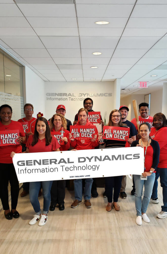 GDIT employees showing support for the Washington Nationals in the office with shirts and signs