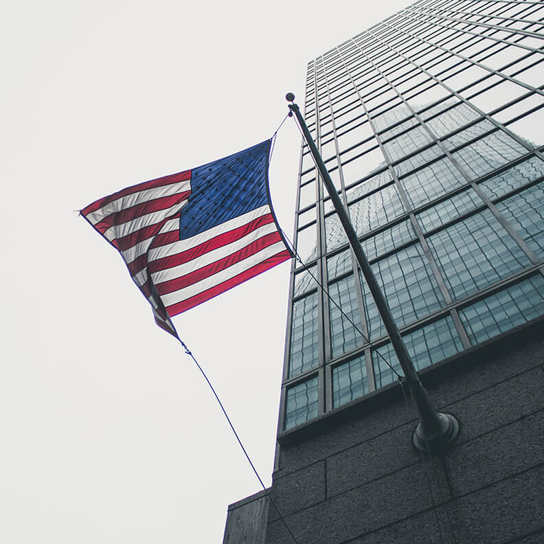 american flag on a tall city building