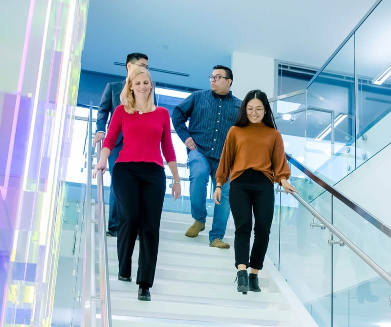 group of four people walking down a staircase