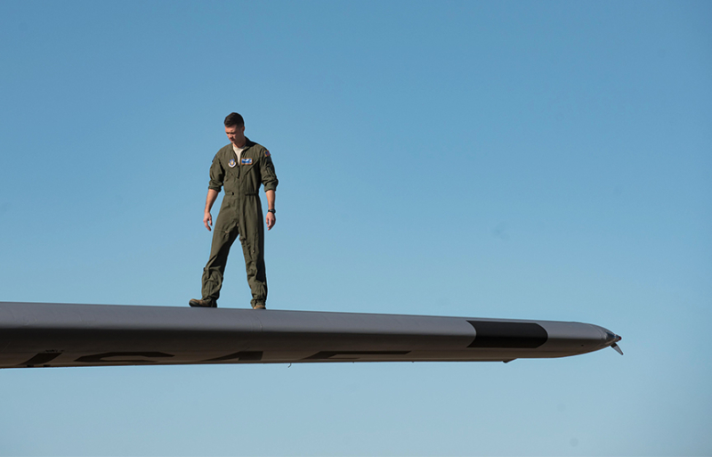 young military man in uniform standing on the wing of a plane