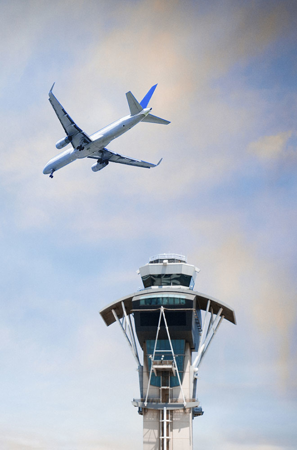Airplane in the sky and an air traffic control tower.