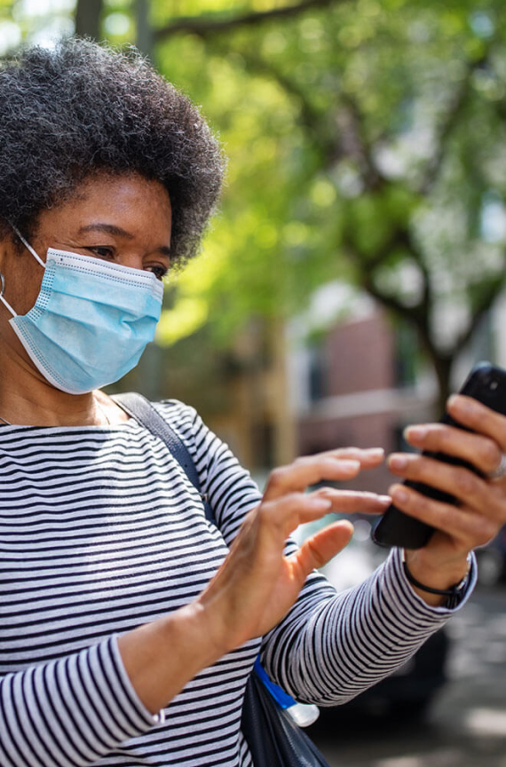 person with face mask looking at cell phone