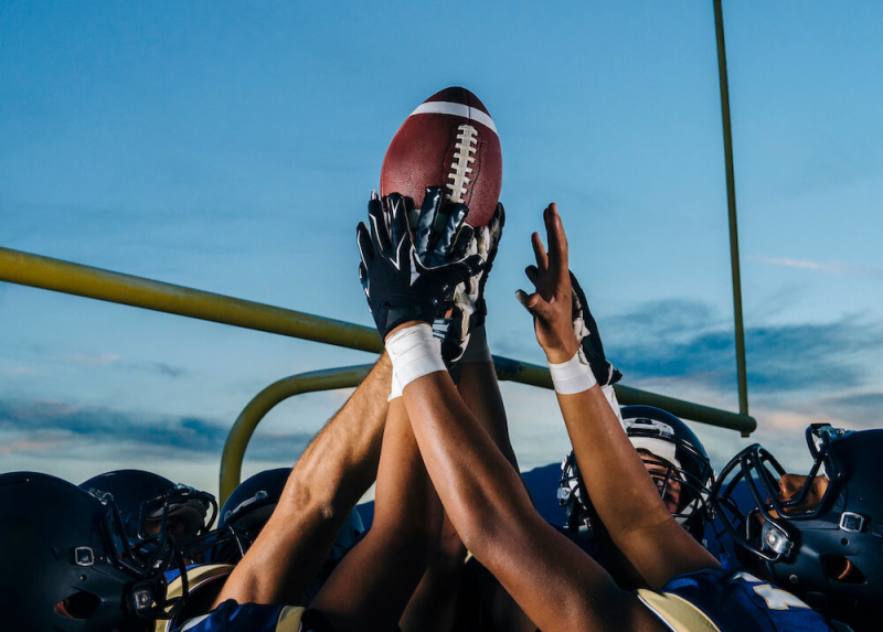 group of football player's hands holding up a football