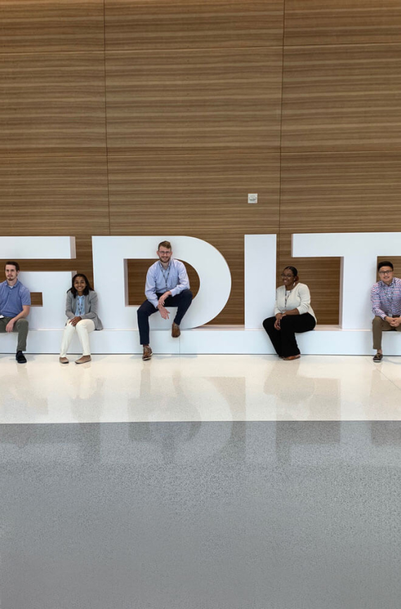 Group of GDIT interns sitting on GDIT lettering display