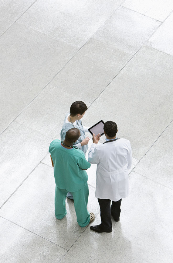 Group of doctors talking around a tablet.