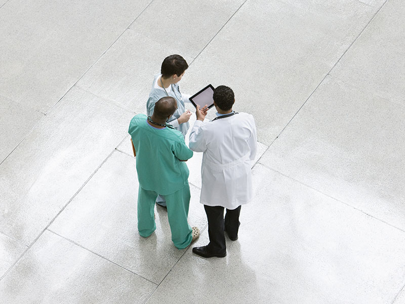 group of doctors talking around a tablet