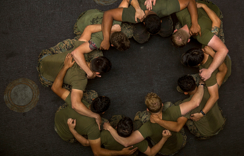 men in military uniforms standing in a circle with their arms around eachother