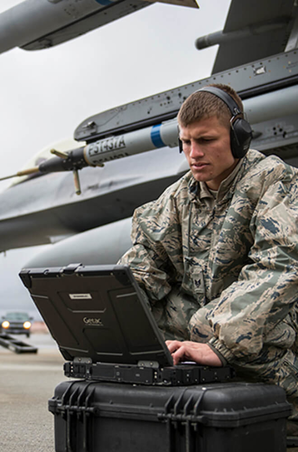 young man in military uniform on laptop in front of a plane
