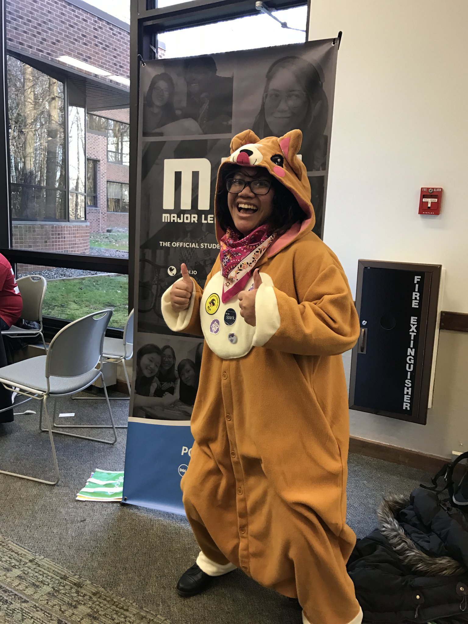 In this picture, I'm standing in front of a Major League Hacking (MLH) sign. I'm at HackHERS 2016 at Rutgers University, Cook Campus Center.I'm wearing a baggy corgi kirigurumi (a fleece character onesie), square rimmed glasses, and a pink bandana. I have several MLH stickers on the chest part of my kirigurumi. I'm giving a double thumbs up to the camera.