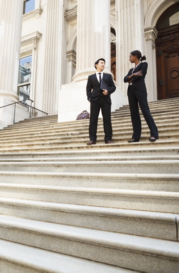 two lawyers standing in front of law building