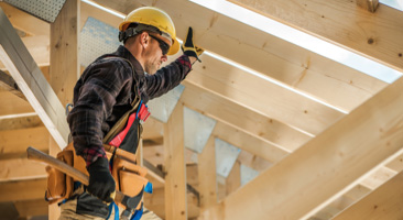 man holding up wooden beam at construction site