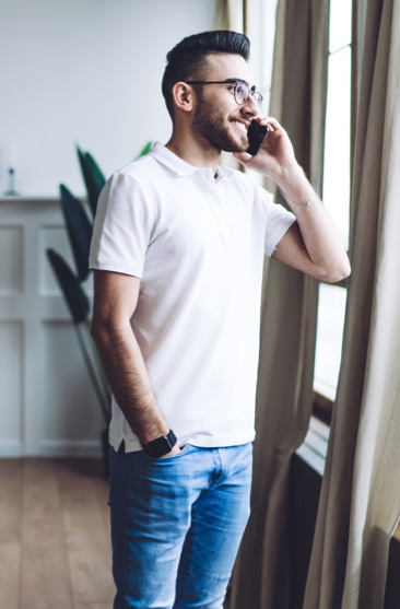 man standing at window while on phone