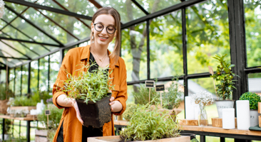 Image of a gardener tending to her plant in a green house