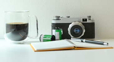 Image of a camera on a desk next to a cup of coffee and a journal