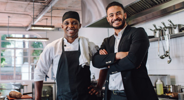 chef standing next to restaurant manager in a kitchen