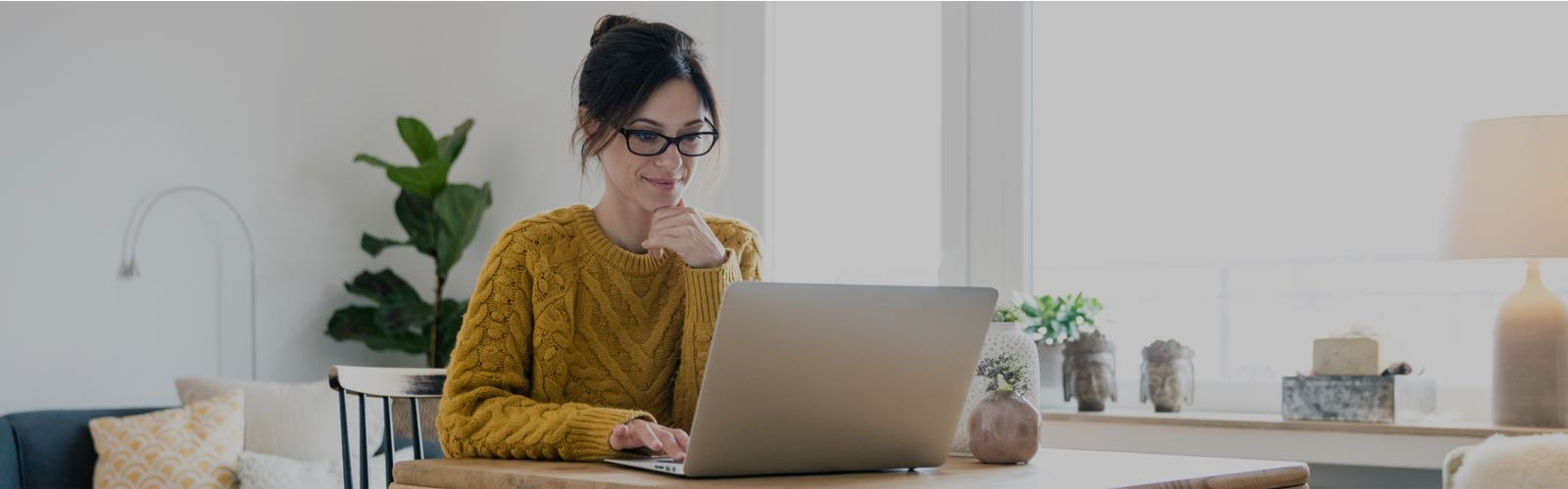 woman in a yellow sweater sitting at a laptop