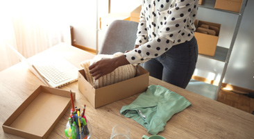 person packing a gift box with clothes