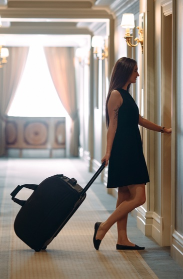 Woman walking into her hotel room with luggage