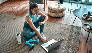woman working out on the floor next to her computer