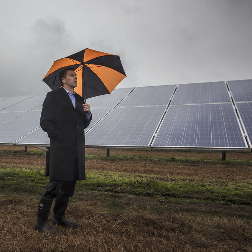Photograph of a man with umbrella walking by solar panels