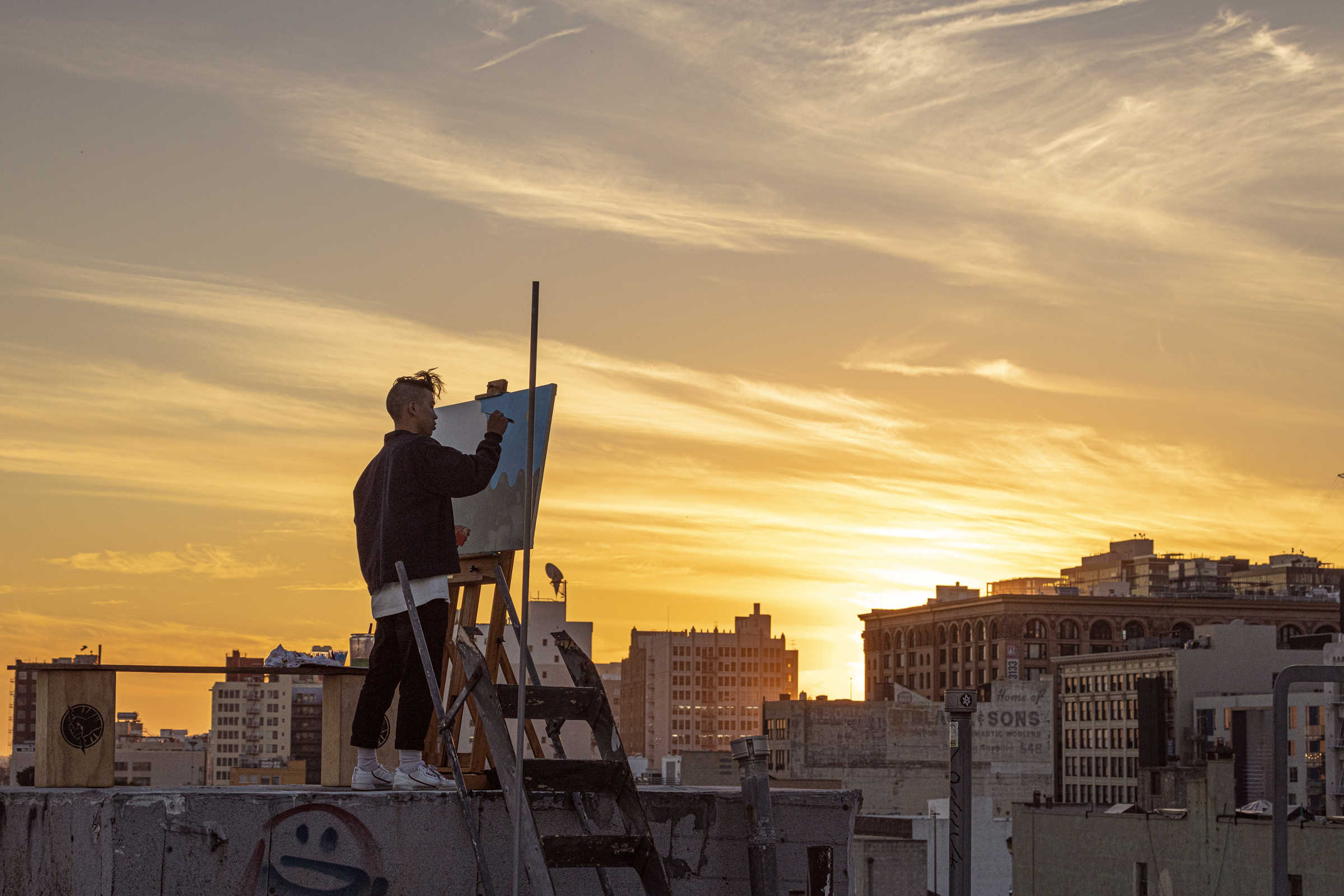 Young man painting on a city rooftop at sunset