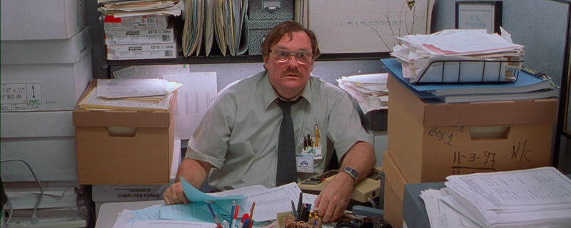A movie still of Office Space of a man looking scared at a desk