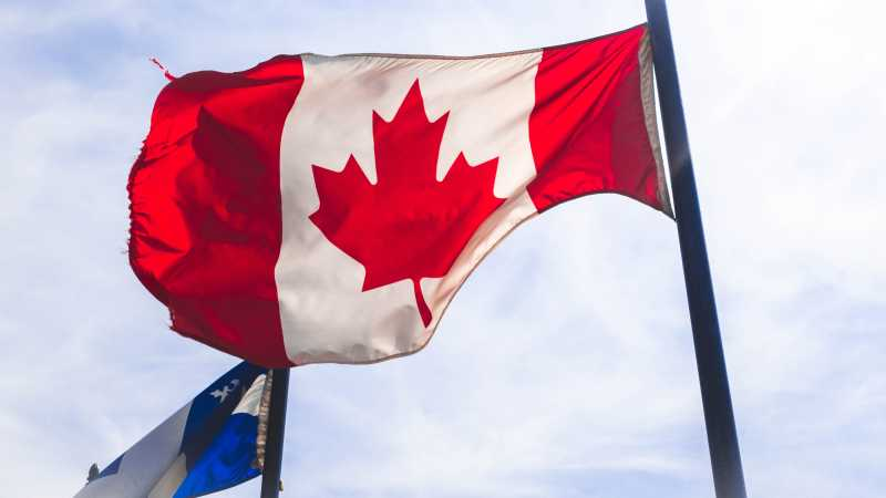 Photo of the Canadian flag on a flagpole