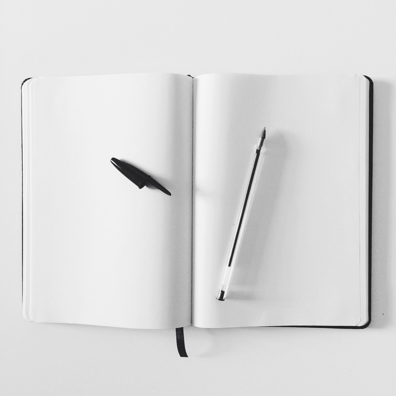 An open notebook with two blank pages. An uncapped pen rests on the paper, asking to be used.