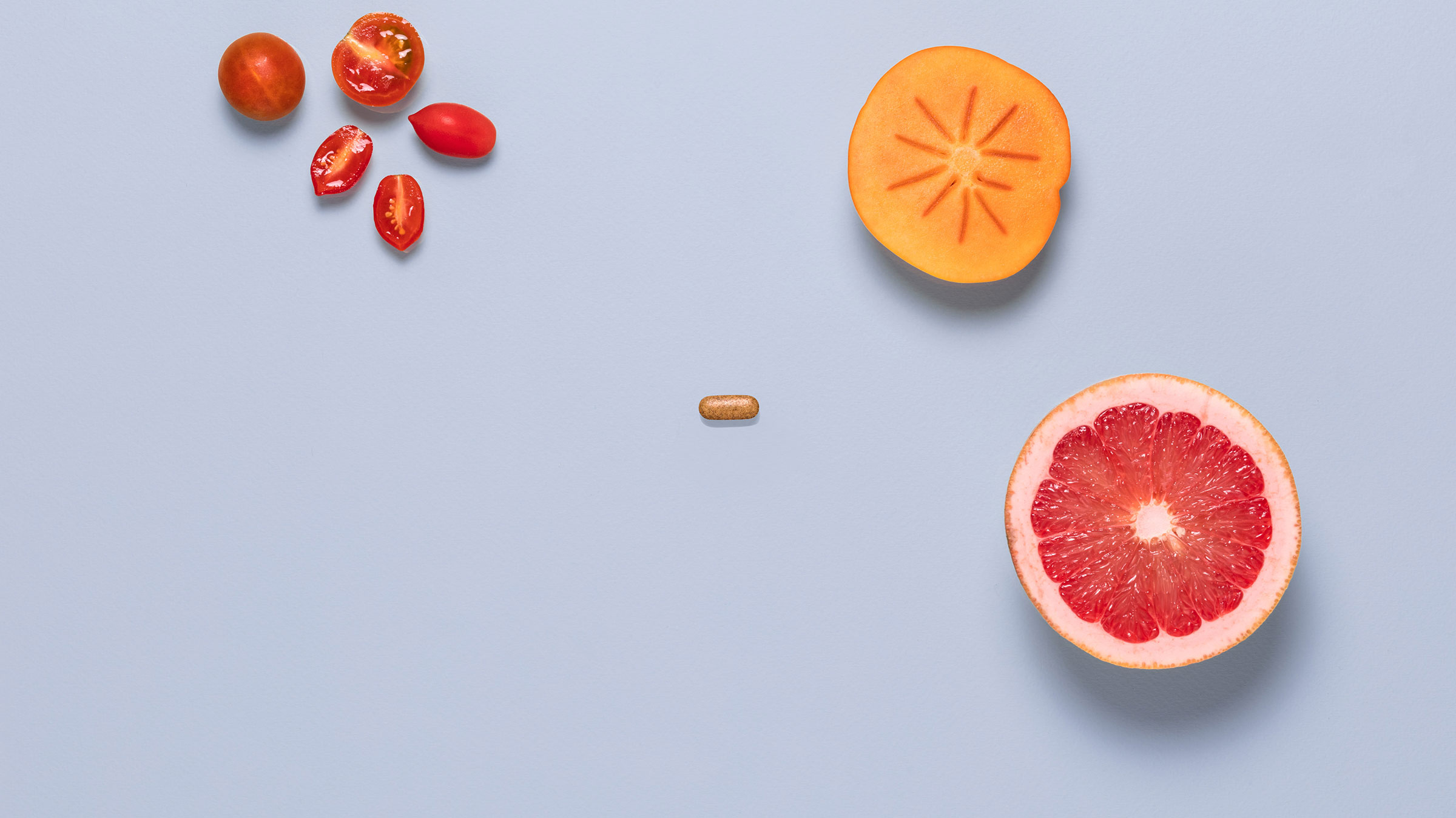 A photo of cherry tomatoes, cantaloupe, an orange slice, and a vitamin C pill laid flat.