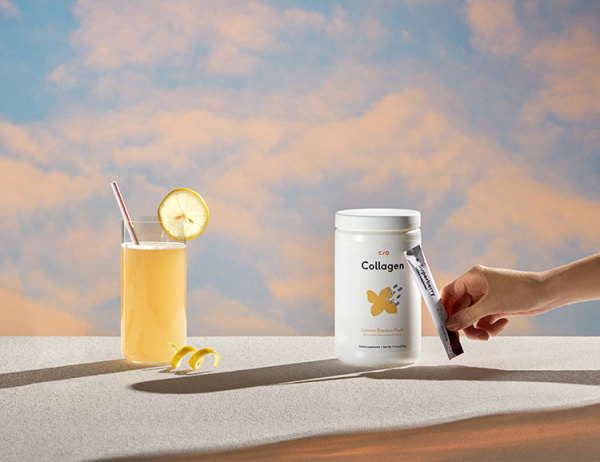 Photo of collagen powder tub and packet with a lemon drink and evening sky backdrop