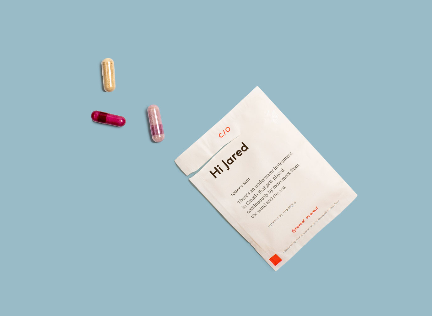 Vitamin pack with beige, red, and pink pills on a pale blue background
