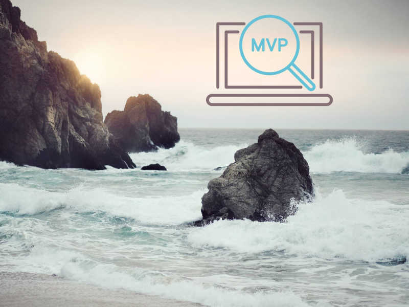 MVP icon in the front, Seashore with small waves crashing at the rocks at sunrise in the background.